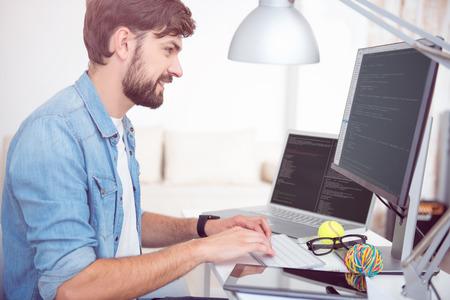 즐거운 일. 테이블에 앉아서 컴퓨터에서 프로그래밍을하는 즐거운 젊은 남자