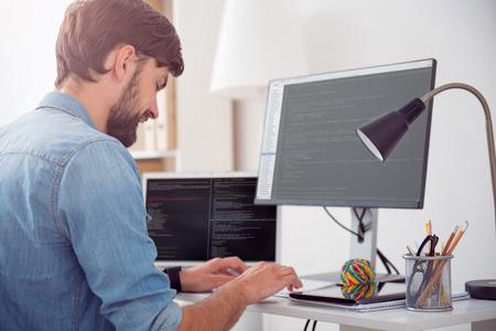 私の仕事がある幸せ。彼の職場で座っている間彼のコンピューターでコードを書く喜んで若い男