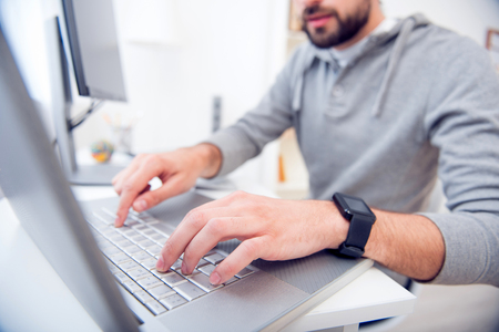 Adding the last details. Close up picture of hands of a bearded man tapping on the laptop while sitting at the table Stock Photo