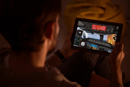 videogame: Some fun. Top view of a man holding a tablet and playing a videogame during the nighttime