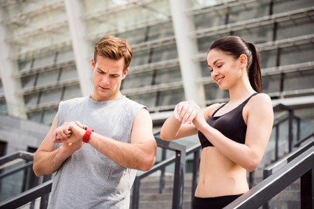 frowning: Time for training. Frowning man and smiling woman touching their watches while preparing for jogging