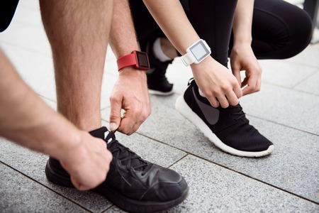 necessary: Necessary steps. Picture of legs of a man and a woman tying shoelaces on their sneakers before jogging