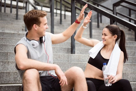 contended: Give me five. Contended young man giving five to lovely young woman while sitting on the stairs after doing sports Stock Photo