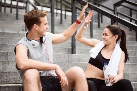 Tape la. jeune homme donnant cinq à A SOUTENU belle jeune femme alors qu'il était assis sur l'escalier après avoir fait le sport Banque d'images
