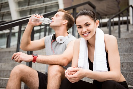 contended: Get some relaxation. Cute young woman looking at camera near a man drinking water while having a rest after exercising Stock Photo