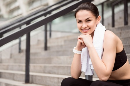 contended: I am in a good shape. Charming young woman looking at camera while sitting on the stairs after a fitness Stock Photo