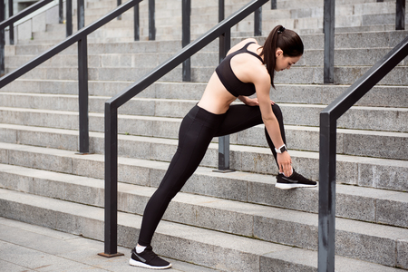 contended: Get ready. Young woman touching her sneakers while standing in the stairs and preparing for jogging in the city Stock Photo