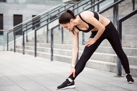contended: I am ready to be the first. Young sport woman stretching before running in the city