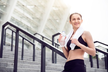 contended: Nice weather for jogging. Contended pretty young woman holding a bottle of water and a towel after working out in the city