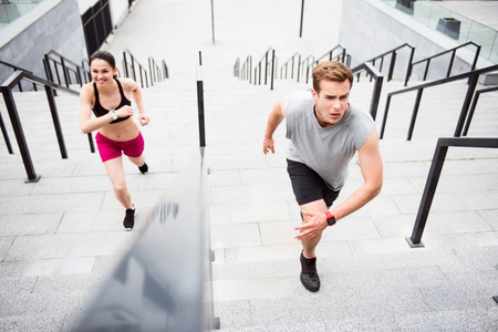 strained: What a nice training. Strained young man and smiling young woman running on the stairs in the city Stock Photo