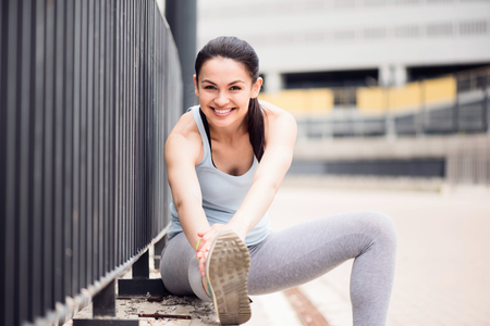 contended: How nice. Magnificent young smiling woman sitting and stretching before running in the city while looking at the camera