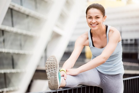 contended: I am good at it. Charming young smiling woman stretching before running in the city while looking at the camera