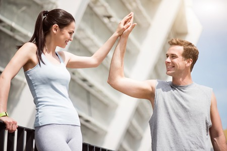 contended: Team spirit. Happy young guy giving high five to a pretty woman after working out with her