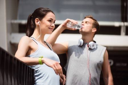 contended: It is a good day. Pretty tired young woman listening to music after working out while a man drinking water in the background Stock Photo
