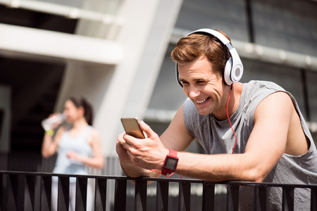 contended: To be in touch. Cheerful pleasant young man using a headset and looking at his phone while a woman drinking water in the background