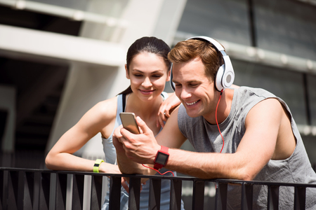 Time together. Lively young man using smartphone while jogging