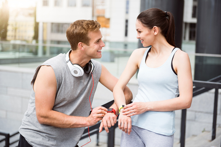 contended: Always connected. Contended young man looking pleasantly at a cute young woman, they touching their smart watches