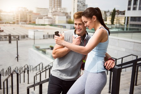 say cheese: Say cheese. Beautiful young sport woman and joyful young man looking at the phone while making a selfie after a training Stock Photo