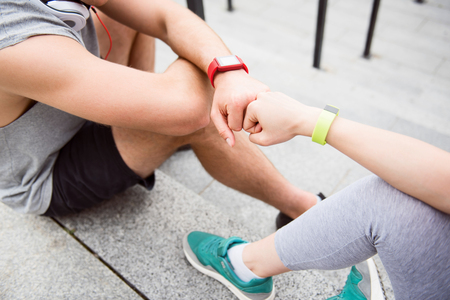 give me five: Give me power five. Young man and healthy woman fist bumping after a good workout while having a rest on the stairs Stock Photo