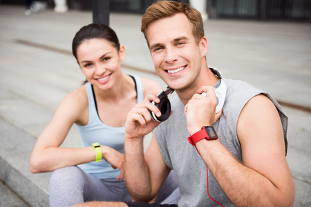 contended: Happy together. Young attractive couple sitting on the stairs and having a rest after working out outdoors