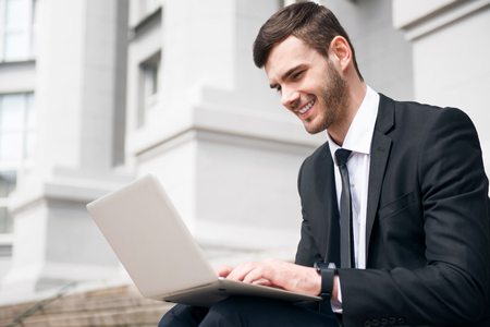 gladness: Like my work. Cheerful delighted smiling man sitting on the footsteps and expressing gladness while using laptop Stock Photo