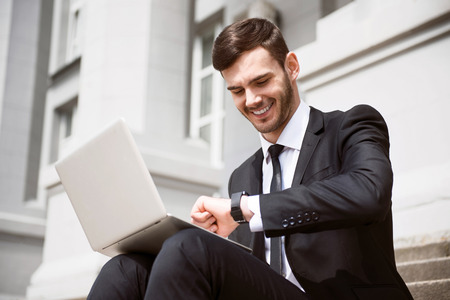 personal digital assistant: What time is it. Pleasant cheerful smiling businessman sitting on the footsteps and using his smartwatch while working on the laptop