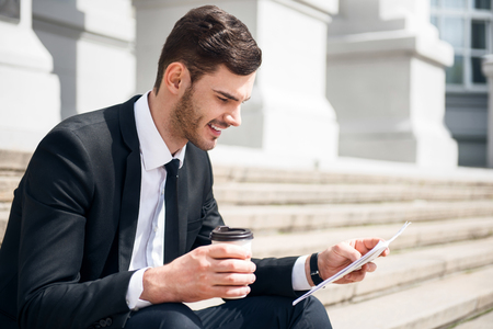 personal digital assistant: Get some rest. Pleasant delighted smiling man sitting on the footsteps and holding papers while drinking coffee