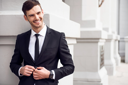 Positive worker. Pleasant handsome cheerful man hooking his jacket and smiling while leaning on the wall Stock Photo