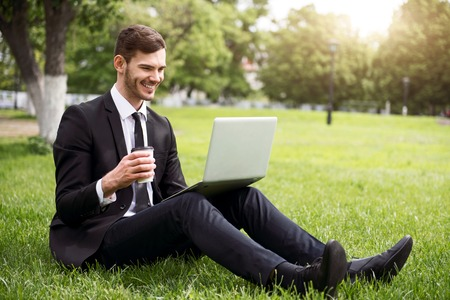 personal digital assistant: Be close to nature. Cheerful delighted handsome smiling man sitting on the grass and using laptop while drinking coffee Stock Photo