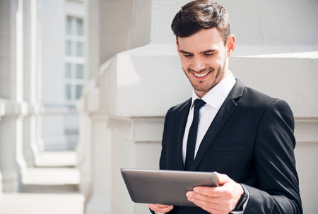 personal digital assistant: Modern way of life. Cheerful content smiling man using tablet and expressing gladness while leaning on the wall
