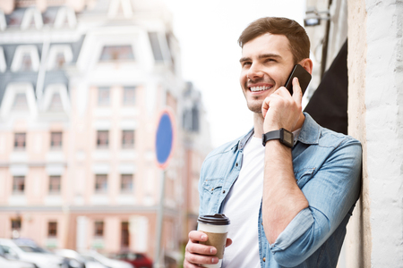 talkative: Talkative person. Cheerful delighted handsome man talking on cell phone and holding coffee while standing in the street