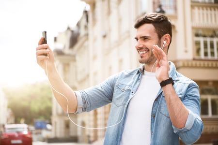 elated: Hey. Cheerful elated smiling man holding cellphone and talking through the Internet while having a walk Stock Photo
