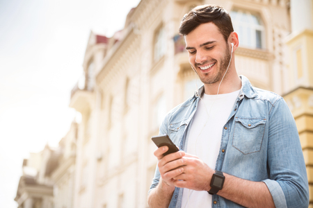 overjoyed: Happy time. Overjoyed handsome smiling man holding cell phone and listening to music while having a walk