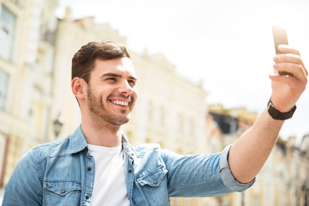 gladness: Say cheese. Positive handsome smiling man holding cellphone and making selfie while expressing gladness
