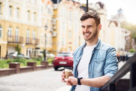 expressing joy: Life lover. Cheerful handsome smiling man drinking coffee and expressing joy while leaning on the handrail