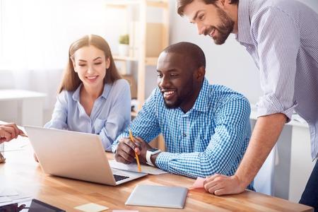 atmosfera: Ambiente amistoso. Colega sonriente de contenido positivo usando la computadora portátil y trabajando en el proyecto mientras que se sienta en la oficina