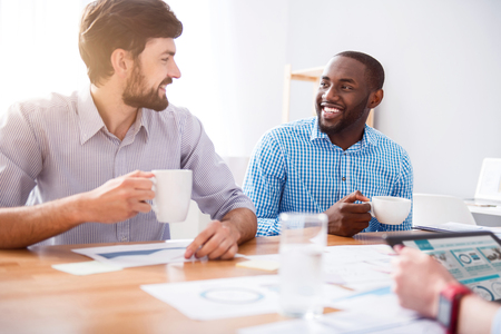 way of thinking: Positive way of thinking. Positive content smiling colleagues sitting at the table and drinking coffee while resting together Stock Photo