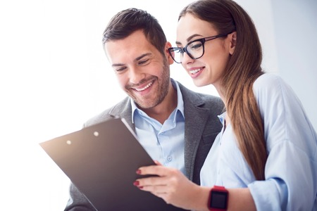 overjoyed: In a good mood. Delighted overjoyed smiling colleagues holding folder and talking while working together Stock Photo