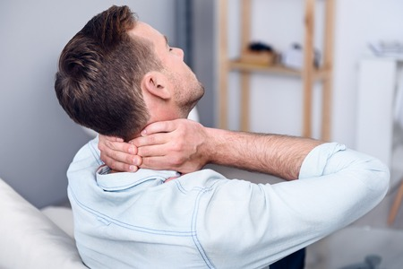 cheerless: I need help. Cheerless sick man sitting on the couch and touching his neck while feeling pain