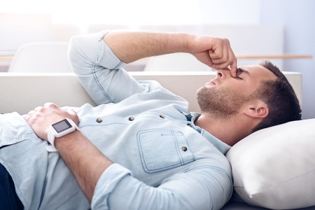 cheerless: Killing pain. Sick cheerless man holding his hand on the face and closing his eyes while lying on the couch Stock Photo
