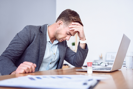 cheerless: I need help. Handsome cheerless sick man touching his forehead and having a headache while sitting at the table Stock Photo