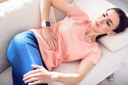 cheerless: Your disease eats your inside, Sick cheerless woman holding her hand on the stomach and feeling ache while lying on the couch Stock Photo