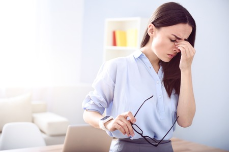 cheerless: Out of energy. Beautiful cheerless woman having a headache and holding her glasses while standing in the office