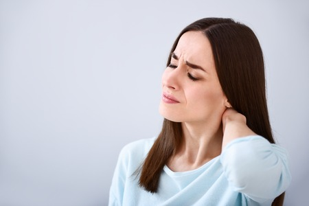cheerless: Relieve your pain. Sick cheerless woman touching her neck and feeling pain while standing isolated on white background Stock Photo