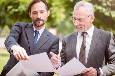 pleasant: Show it to me. Pleasant busy colleagues standing outside and holding papers while working together Stock Photo