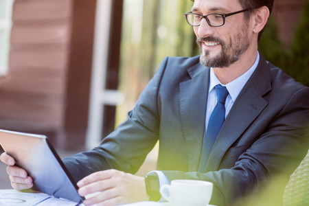 overjoyed: Express yourself. Pleasant handsome overjoyed man sitting at the table and using tablet while feeling glad Stock Photo
