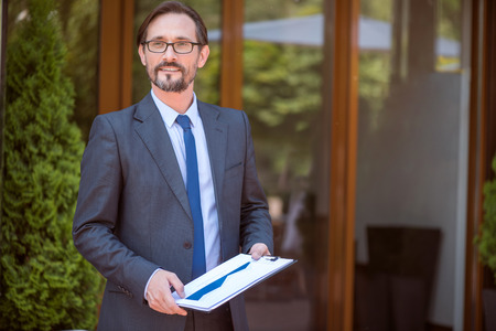 pleasant: Confidence in mind. Pleasant delighted handsome man holding folder and looking aside while standing outdoor Stock Photo