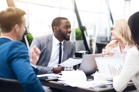 common goal: Set common goal. Pleasant delighted involved colleagues sitting at the table and talking while discussing project Stock Photo
