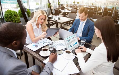 diligente: ambiente de trabajo. colegas diligentes agradables sentado en la mesa y participar en el trabajo