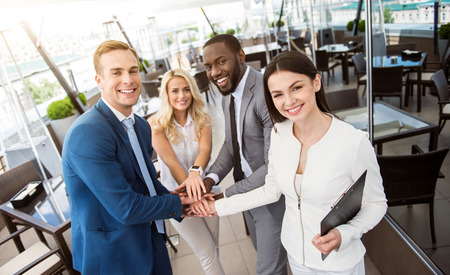 work together: Ready to work. Pleasant cheerful colleagues holding hands together and expressing joy while smiling